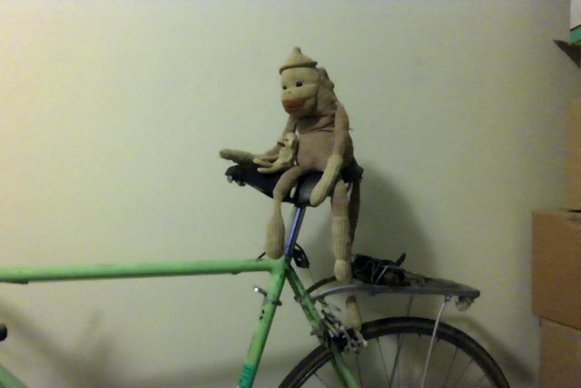 Two sock monkeys sitting on a bicycle.