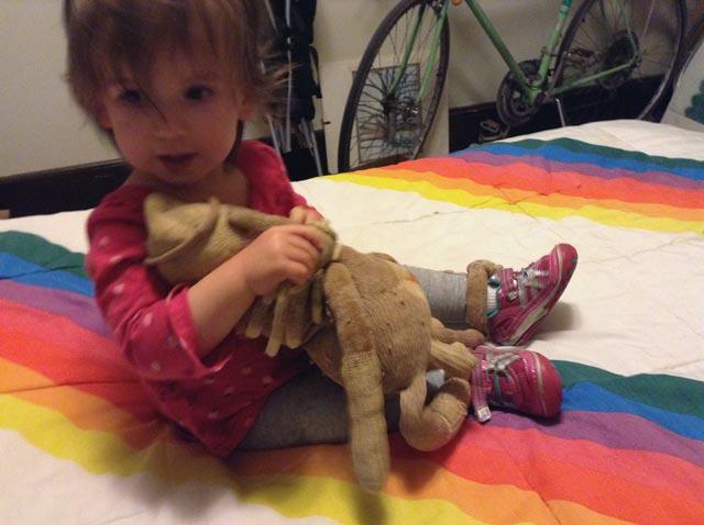 Toddler hugging two sock monkeys.