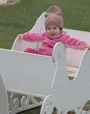Grand daughter smiling in a wooden sleigh at the park.