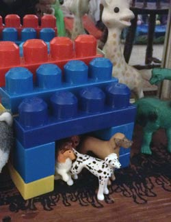 A simple lego dog house with several plastic dogs.