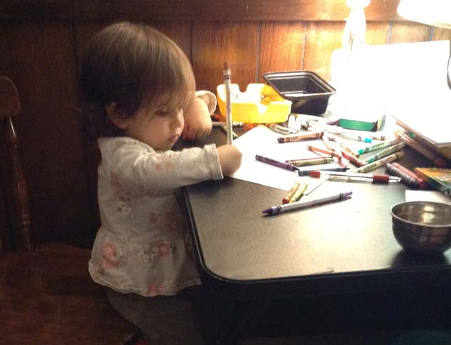 Toddler seated at a card table using pencils and crayons.