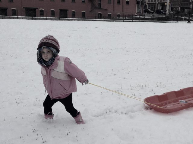 Child dragging plastic toboggan.