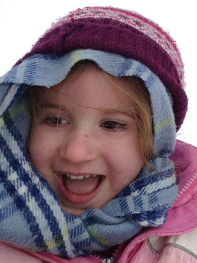 Child wrapped in a scarf, with knit cap.