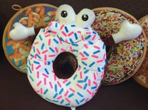 Photo of a donut mascot pillow.