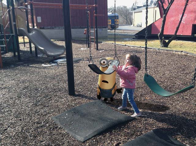 Granddaughter on the swing with an imaginary character.