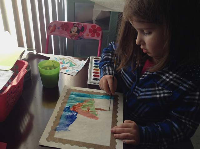 Granddaughter at work, painting.